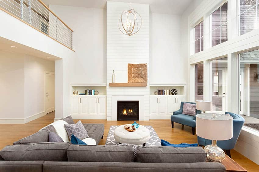 High ceiling living room with large sectional sofa round ottoman wood floors fireplace blue armchairs