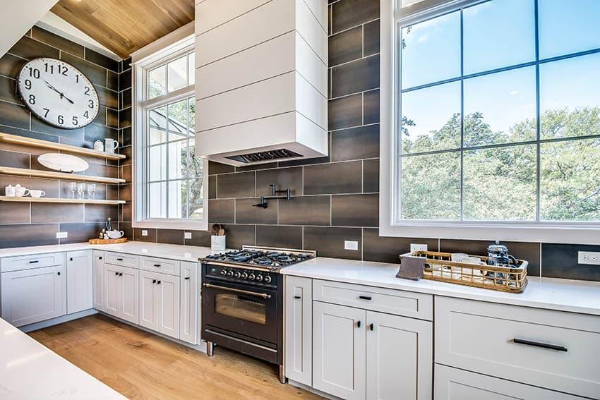 Kitchen with matte black pot filler faucet white shaker cabinets large rectangular tile backsplash