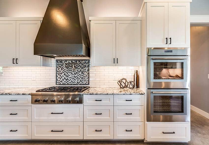 Kitchen with stainless steel pot filler faucet white shaker cabinets white subway tile backsplash mosaic tile backsplash inlay