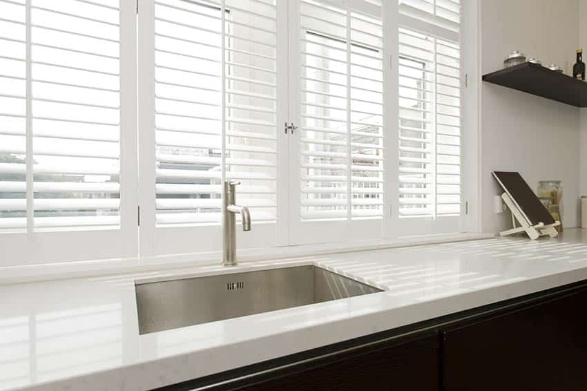 Kitchen with window blinds above sink