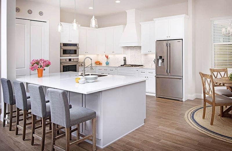 L shaped kitchen white cabinets white quartz countertops wood look flooring