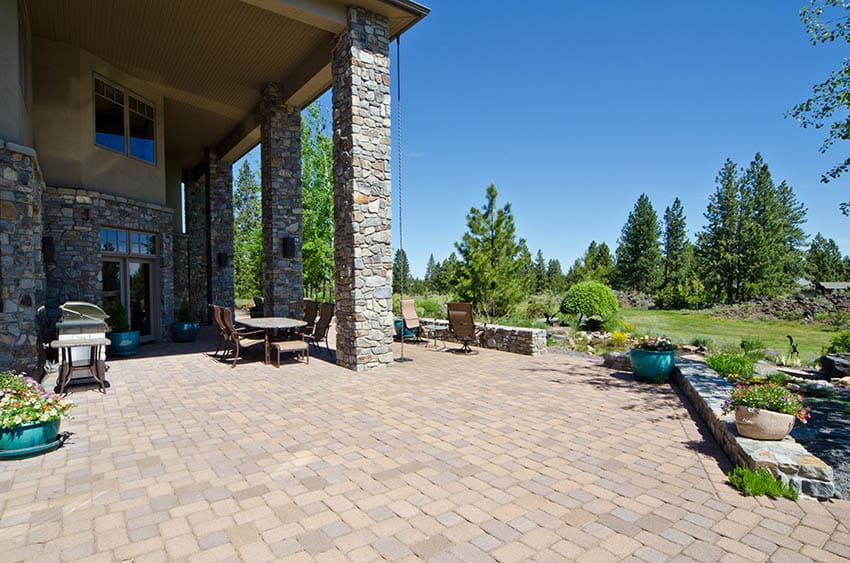 Large backyard paver patio with covered dining table