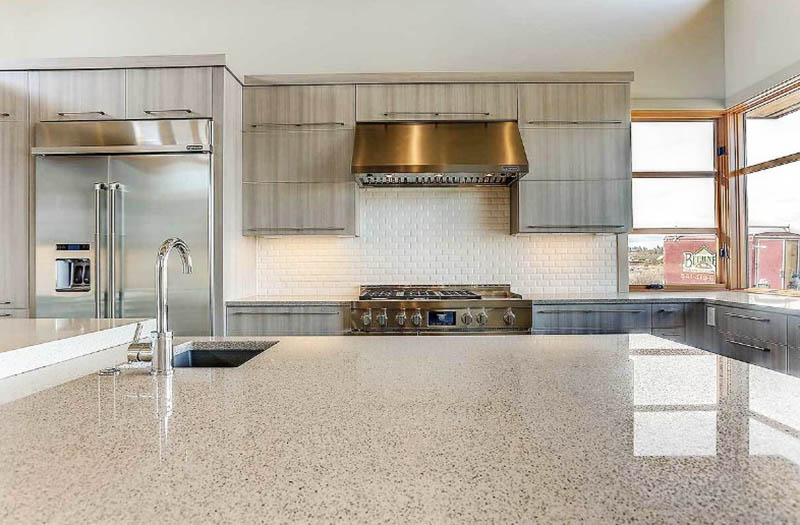 Large quartz kitchen island with built in sink white subway tile over stove