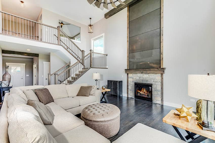 Living room with off white sectional sofa floating way from wall large stone fireplace
