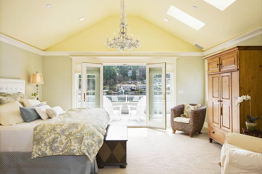 Luxury bedroom with beige wool carpet vaulted ceiling skylights and chandelier