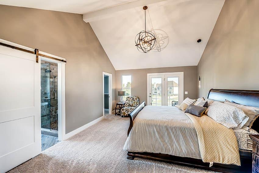 Master bedroom with beige nylon carpet vaulted ceiling globe chandelier white sliding barn doors