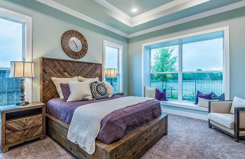 Master bedroom with nylon carpet wood platform bed wrap around windows