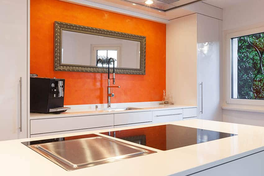 Modern kitchen with corian countertops and orange accent wall with mirror