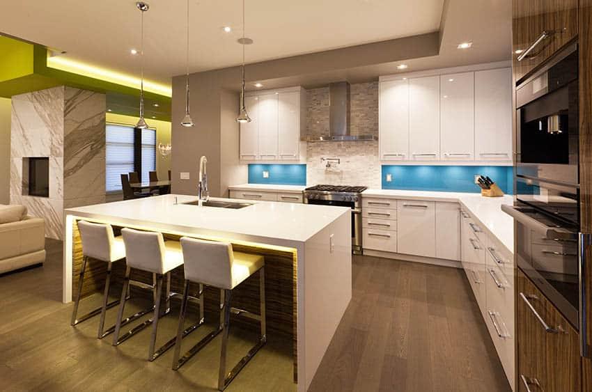 Modern kitchen with white corian countertops under island lighting blue glass backsplash