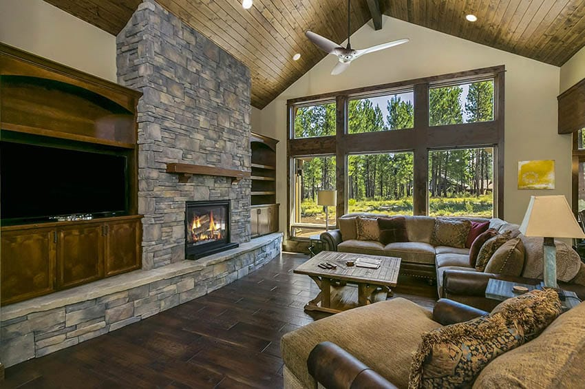 Mountain craftsman living room with vaulted ceiling wood planking stone fireplace wood mantel