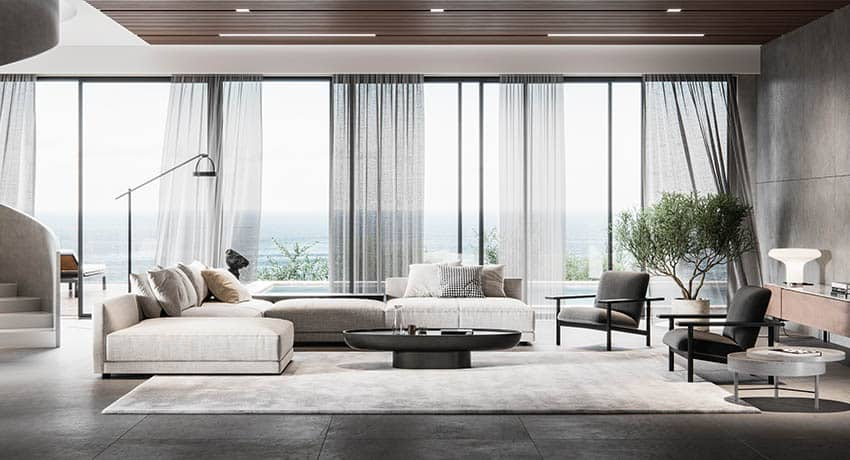 Stylish modern living room with off white sectional sofa black oval coffee table concrete floors