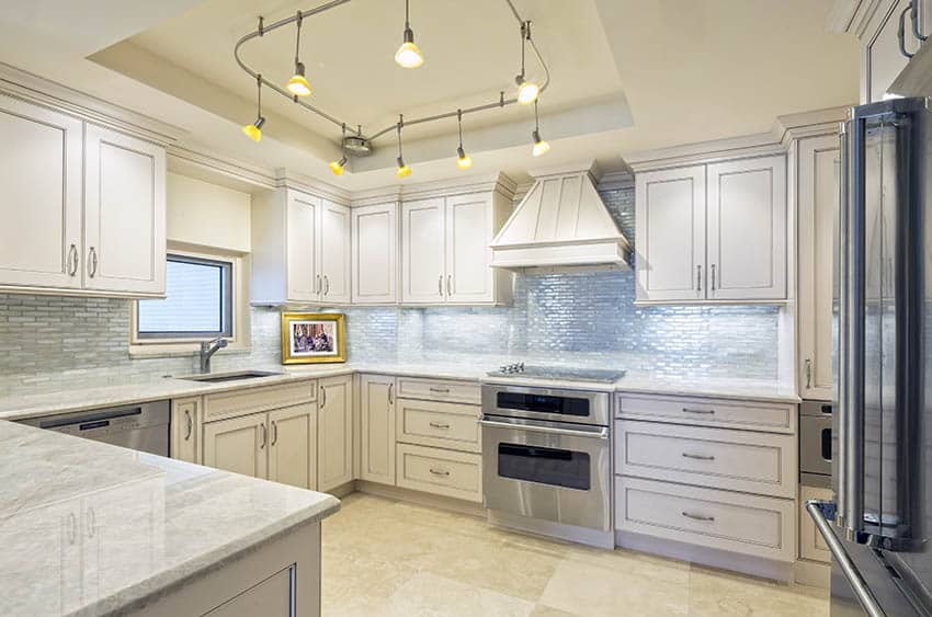 Track lighting ceiling fixture in traditional kitchen with off white cabinets marble countertops