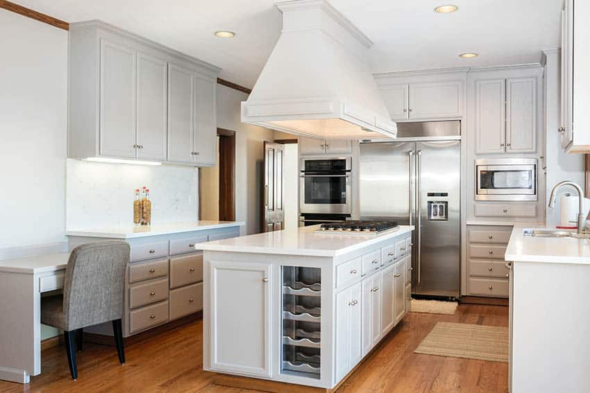 U shaped kitchen with corian countertops light gray cabinets island with cooktop