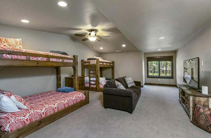 Upstairs bonus room with kids bunkbeds large tv and sofa