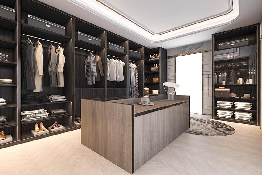 Walk in closet with indirect light in tray ceiling wood veneer island