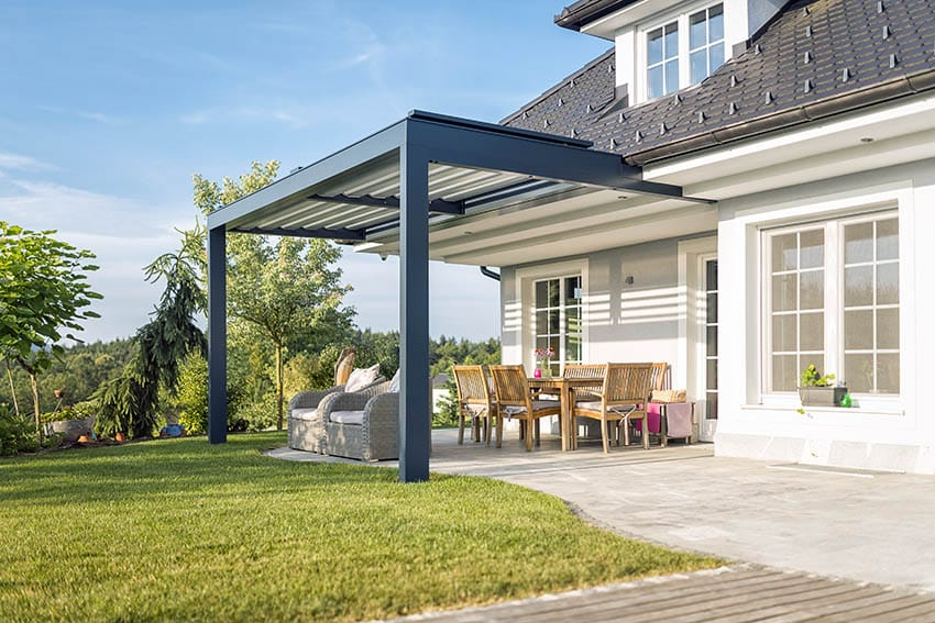 Backyard travertine patio with metal pergola attached to house