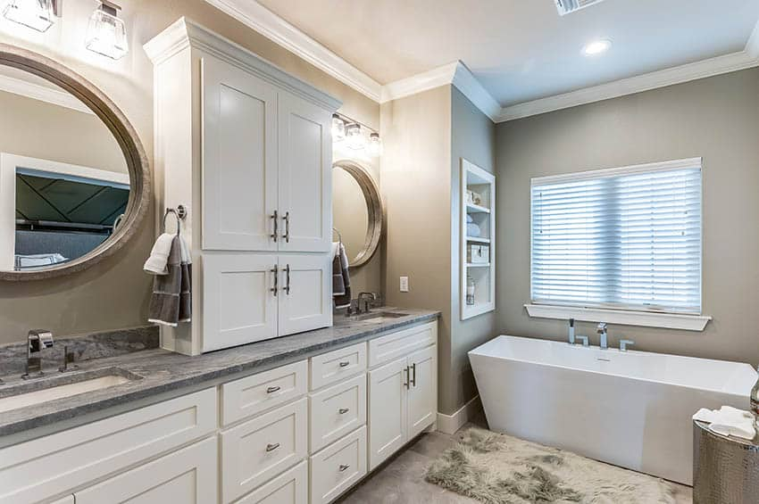Bathroom with dual vanities waterfall faucets white cabinets contemporary tub