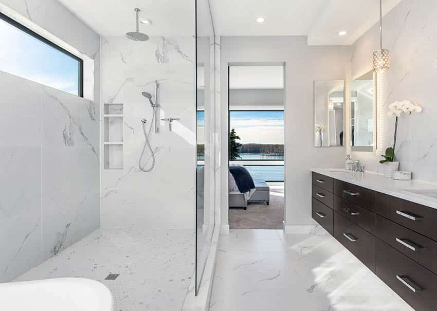 Bathroom with white quartz shower walls rainfall shower head and brown floating vanity with under cabinet lighting