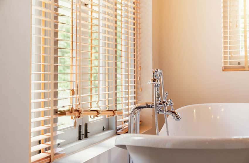 Bathroom with window blinds above tub