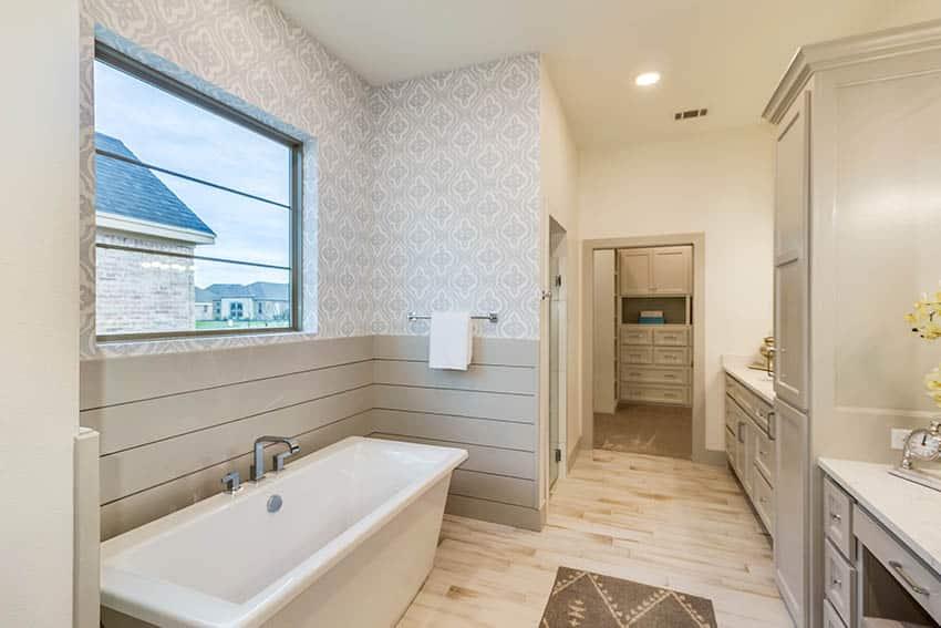 Bathroom with wood look vinyl sheet flooring grey shiplap walls and patterned wallpaper