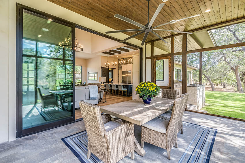 Bluestone patio with wood plank ceiling outdoor dining table large indoor outdoor sliding door living space