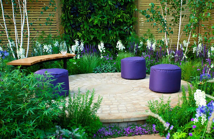 Circular raised paver patio with curved wood bench and flowering plants