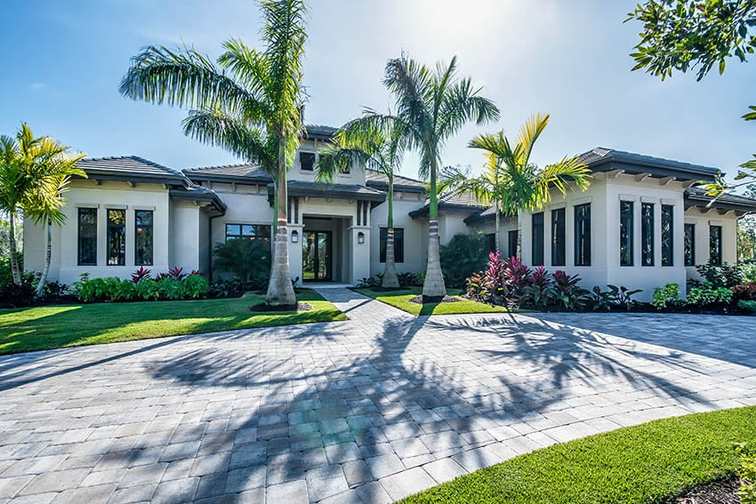 Contemporary home with paver driveway palm trees tropical landscaping