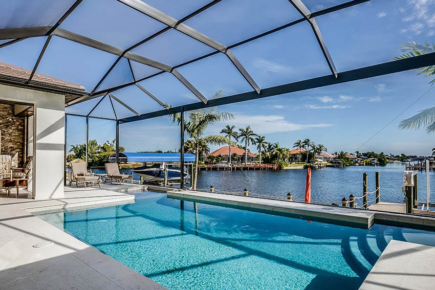 Covered backyard swimming pool with waterfront views
