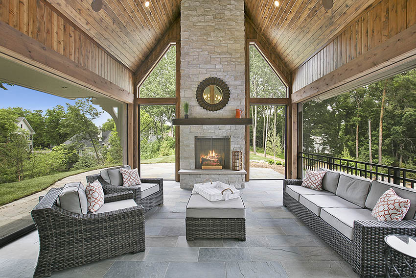 Covered bluestone patio design with vaulted ceiling outdoor fireplace and rattan furniture