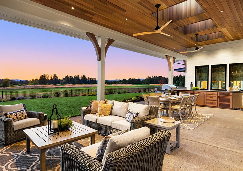 Covered exposed aggregate patio with outdoor furniture golf course views
