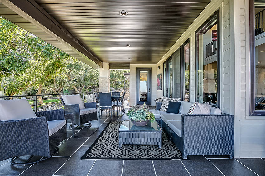 Covered patio with resin wicker outdoor chairs coffee table and sofa with cushions