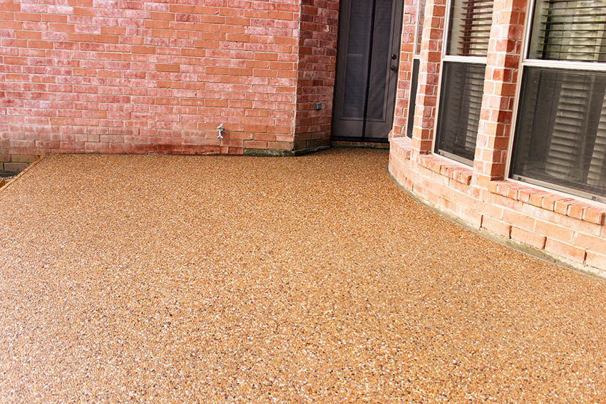 Exposed aggregate patio behind brick home