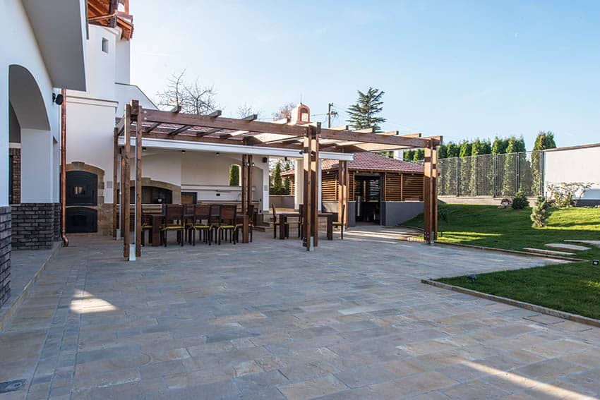 Irregular cut bluestone paver patio with pergola and outdoor kitchen