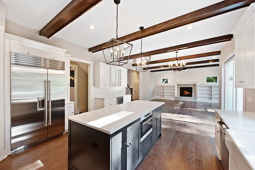 Kitchen with spc flooring white cabinets black island wood beams ceiling