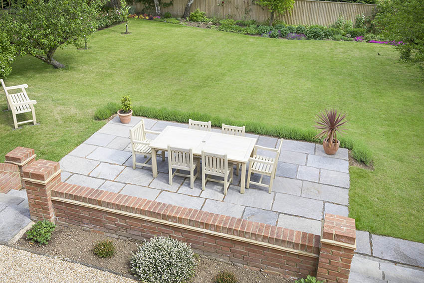 Large bluestone pavers patio with outdoor dining table brick wall