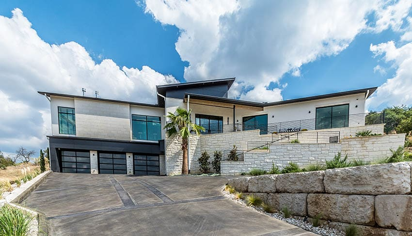 Modern house with sloped concrete driveway 3 car garage and stone wall