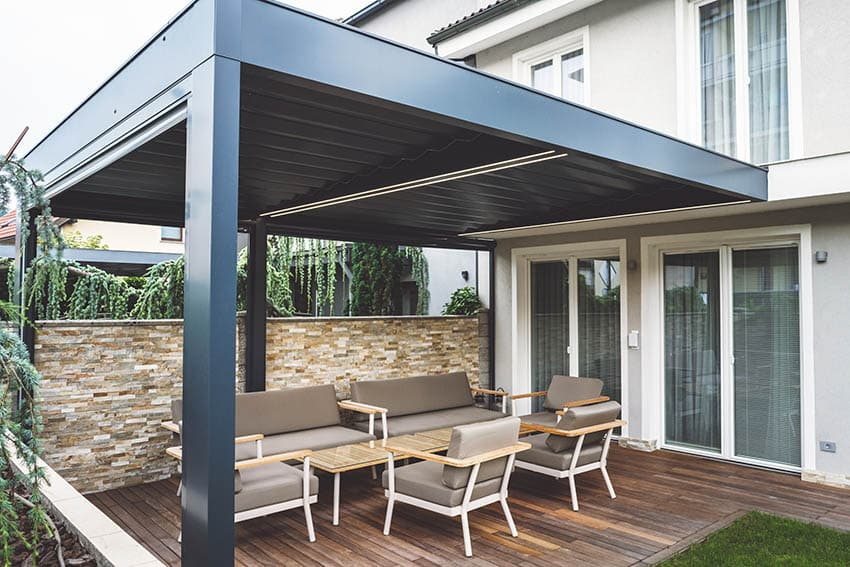 Modern insulated patio cover above wood deck and stacked stone wall