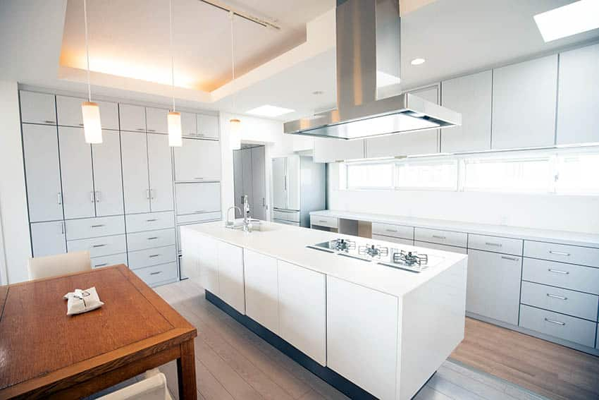 Modern kitchen with white solid surface countertops white island grey cabinets