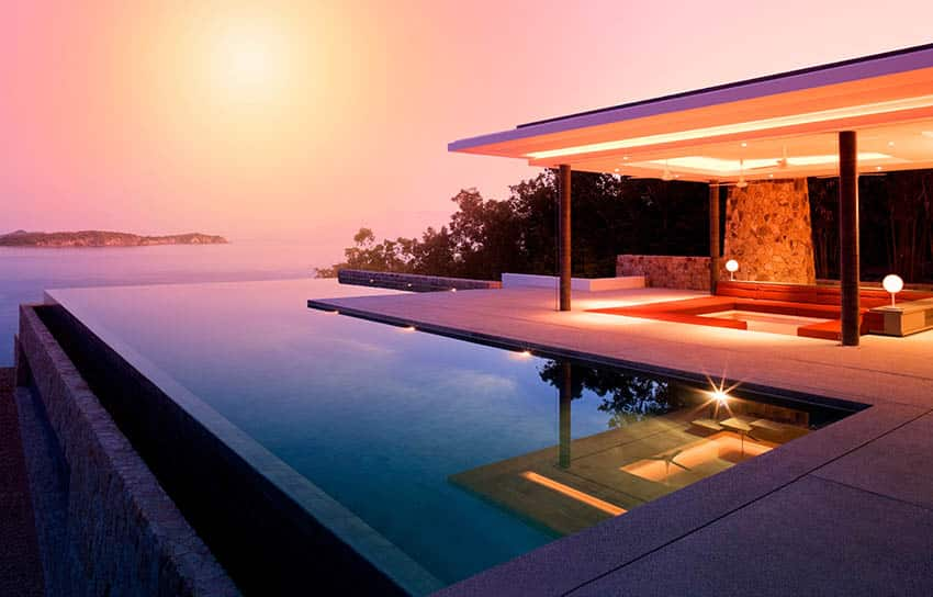 Modern l shaped swimming pool with infinity edge and pavilion