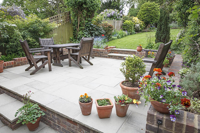 raised-brick-and-concrete-patio-with-wood-dining-table-potted-plants