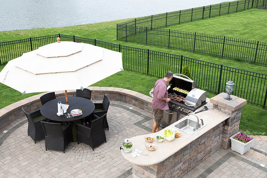 Raised brick paver patio with circular design outdoor kitchen and dining table