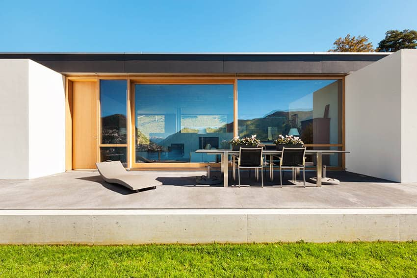 raised-concrete-patio-on-modern-home-backyard-with-outdoor-dining-table