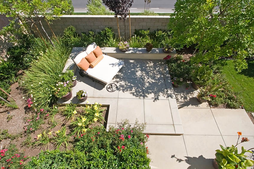 Raised concrete patio with daybed garden landscaping