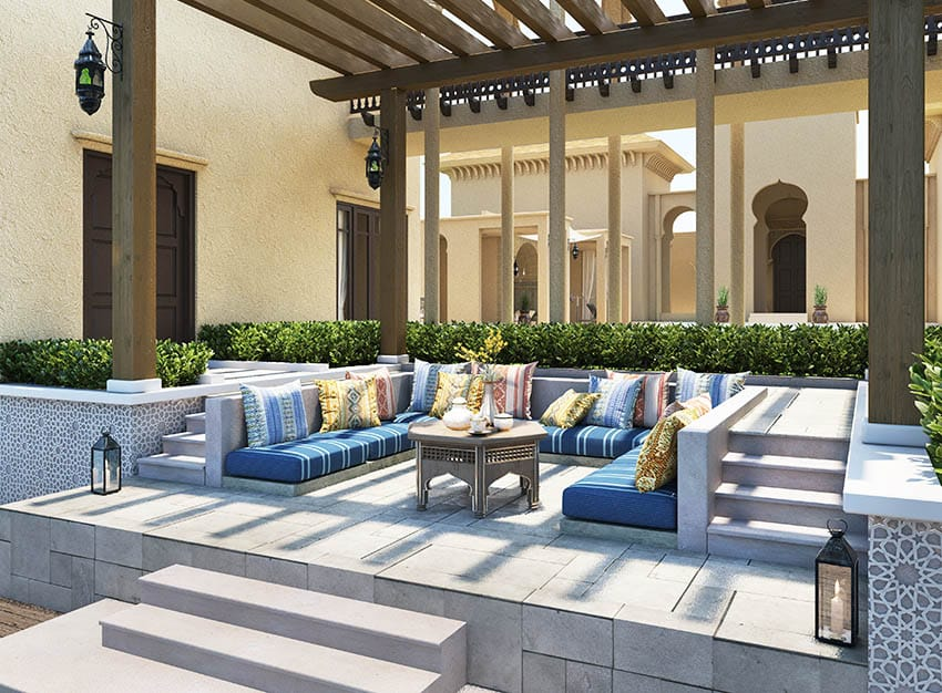 Raised concrete paver patio with pergola and concrete cushioned bench