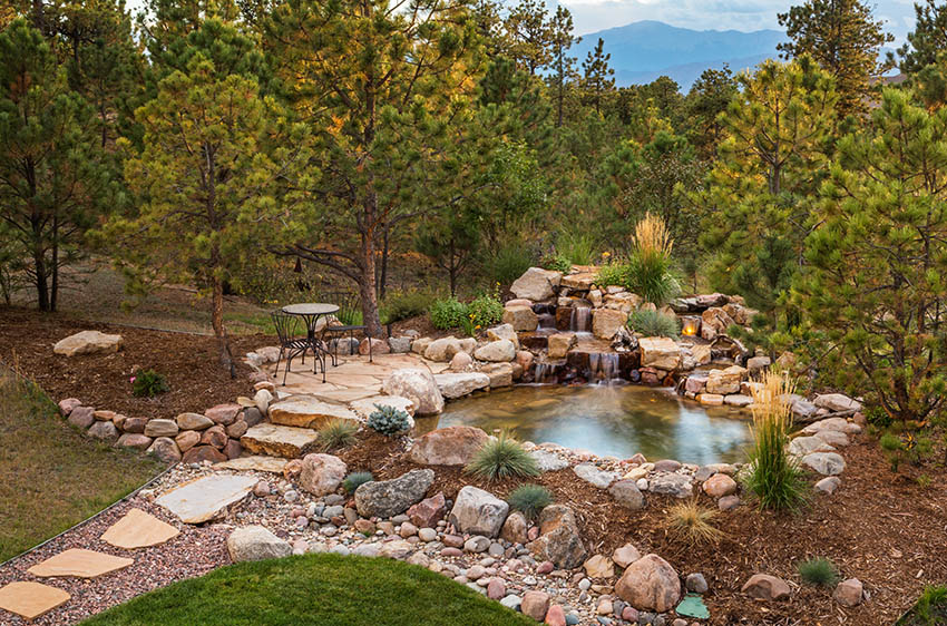 Raised flagstone patio above water feature pond and waterfall