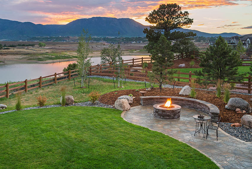 Stamped concrete patio fire pit with stone bench and waterfront river views