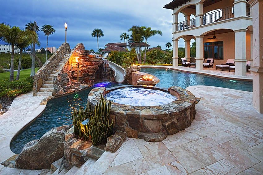 Stamped concrete pool deck patio with elevated hot tub water slide