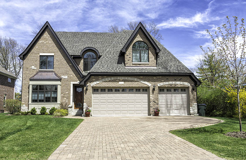 Traditional house with paver driveway three car garage