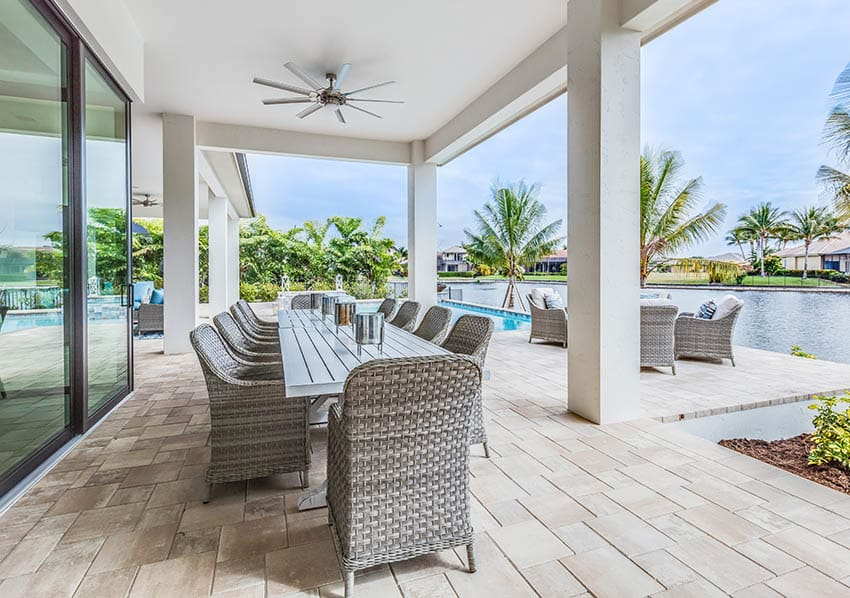 Waterfront travertine patio with rattan outdoor dining table