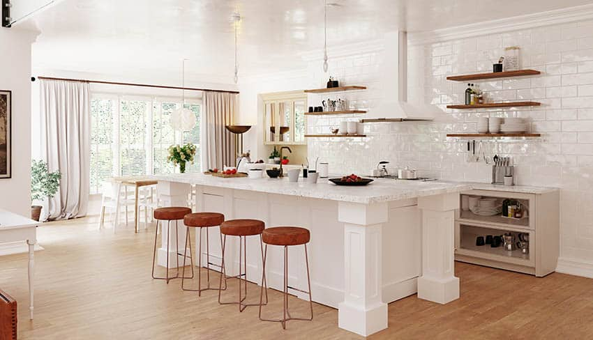White cabinet kitchen with white quartz countertops island with legs and wall of large subway tile